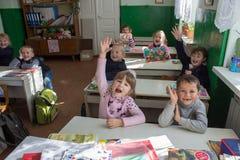 Little schoolchildren raise their hands in the classroom,3.11. 2014 Ukraine Mervichi royalty free stock photos
