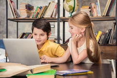 Little schoolchildren studying together and using laptop Royalty Free Stock Photo