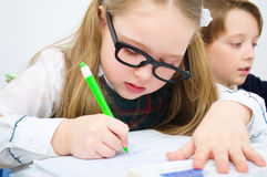 Little schoolchildren writing in workbook Royalty Free Stock Image