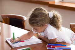 Little schoolgirl. Little girl drawing on the table Royalty Free Stock Image