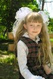 Little schoolgirl. The sitting girl in a school uniform Royalty Free Stock Image