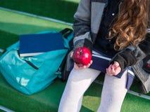 А little schoolgirl with apple ascending to school outdoors stock images