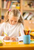 Little schoolgirl behind desk Stock Photography