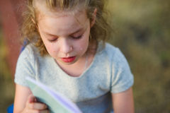 The little schoolgirl cries over a school notebook. The schoolgirl on cheeks has tears. The girl has a sad look Royalty Free Stock Photography