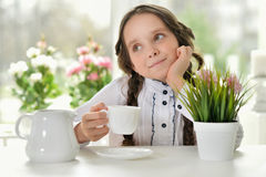 Little schoolgirl drinking tea Stock Photo