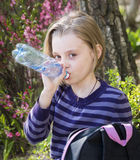 Little schoolgirl  drinks water Stock Photo