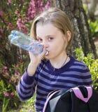 Little schoolgirl  drinks water Stock Photo