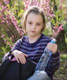 Little schoolgirl  drinks water Stock Photos