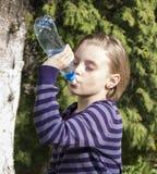 Little schoolgirl  drinks water Royalty Free Stock Photo