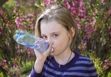 Little schoolgirl  drinks water Stock Photography