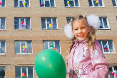 Little schoolgirl with green balloon. In front of the school decorated balloons royalty free stock image
