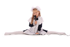 Little Schoolgirl hold black microphone and sitting on the split Stock Image