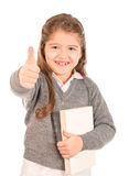 Little schoolgirl holding a book giving a thumbs-up royalty free stock image