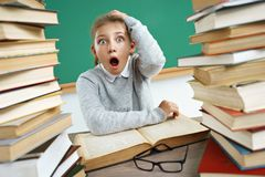 Little schoolgirl holding head with opened mouth and crazy facial expression. Photo of girl in classroom around books. Education concept stock images
