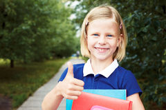 Little schoolgirl holds in hands books and smiling. Royalty Free Stock Images