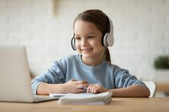 Free Little Schoolgirl Learning School Subject Distantly Using Pc And Headphones Stock Photos - 186899793