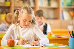 Little schoolgirl during lesson in school Royalty Free Stock Photo