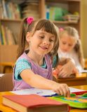 Little schoolgirl during lesson in school Stock Photo