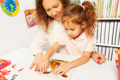 Little schoolgirl pieces together a jigsaw puzzle Royalty Free Stock Images