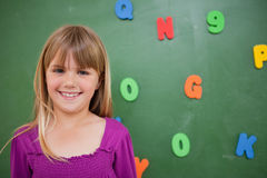 Little schoolgirl posing in front of a blackboard stock photo