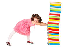 Little schoolgirl push a stack of heavy books Royalty Free Stock Photography