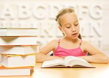 Little schoolgirl reading a book. Royalty Free Stock Image