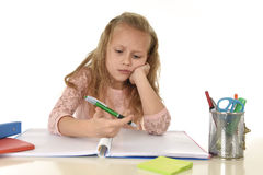 Little schoolgirl sad and tired looking depressed suffering stress overwhelmed by load of homework. Sweet little schoolgirl sad and tired looking depressed Stock Image