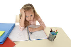Little schoolgirl sad and tired looking depressed suffering stress overwhelmed by load of homework. Sweet little schoolgirl sad and tired looking depressed Stock Images