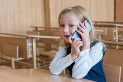 A first grade student at school speaks by phone. emotions of schoolgirls stock image