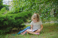 Little schoolgirl sits having crossed legs under a tree and does homework. Royalty Free Stock Photography