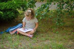 Little schoolgirl sits having crossed legs under a tree and something diligently writes in the notebook Stock Images