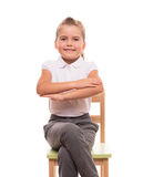 Little schoolgirl sitting on a chair and holding her hands in fr Stock Photo