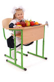 Little Schoolgirl sitting at a desk holding a lot of fruits Royalty Free Stock Image