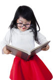 Little schoolgirl studying with a textbook Stock Images