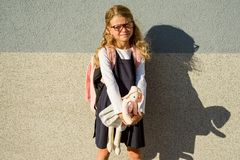 The little schoolgirl took her toy to school with her. Elementary School - Start of classes Stock Photography