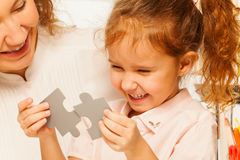 Little schoolgirl tries to assemble jigsaw puzzle Stock Images