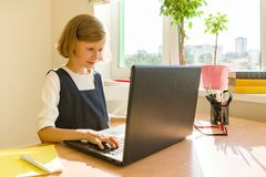 Little schoolgirl uses computer laptop sitting at a desk at home. School, education, knowledge and children.  stock photography