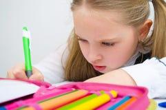 Little schoolgirl writing homework. From school in workbook Stock Photo