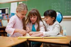 Little schoolgirls reading a fairy tale Stock Photography