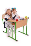 Little schoolgirls sitting at a desk Royalty Free Stock Image