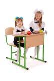 Little schoolgirls sitting at a desk Stock Images