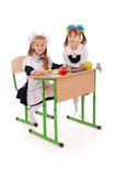 Little schoolgirls sitting at a desk Stock Photography