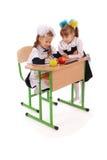 Little Schoolgirls sitting at a desk Royalty Free Stock Photos