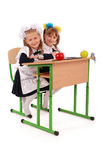 Little schoolgirls sitting at a desk Royalty Free Stock Photo