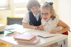 Little schoolkids fool around in class. Royalty Free Stock Photo