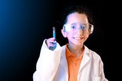 Little scientist. Boy with experiments isolated over dark background Royalty Free Stock Photos