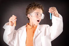 Little scientist. Boy with experiments isolated over dark background Stock Images