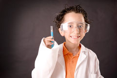 Little scientist. Boy with experiments isolated over dark background Stock Image
