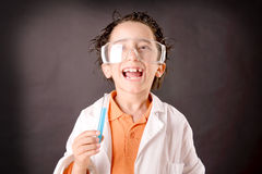Little scientist. Boy with experiments isolated over dark background Royalty Free Stock Image
