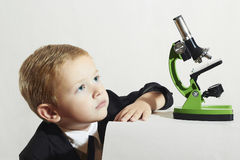 Little scientist.fashion portrait of little boy in tie.stylish child.Schoolboy working with a microscope Royalty Free Stock Images